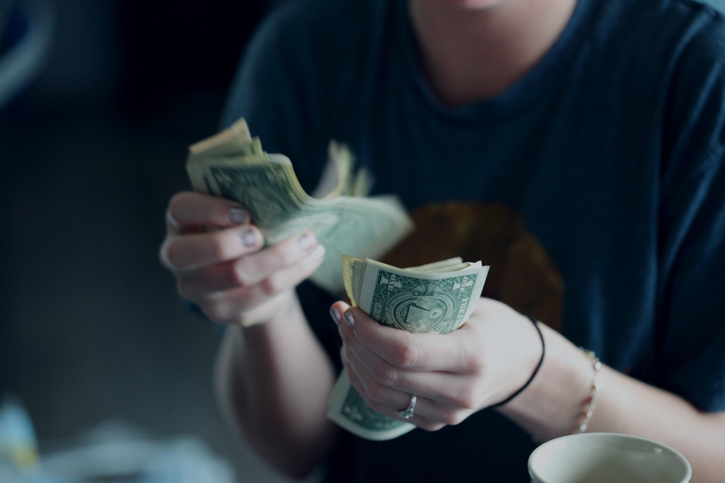 woman in her twenties counting dollar bills during the 127 Corridor Sale
