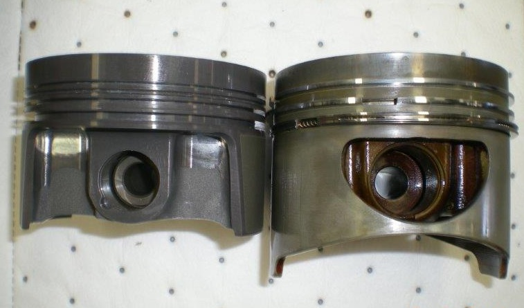 The new Mahle high compression piston on the left, next to the stock and heavier piston on the right. Note the reduction in the skirt area of the new piston.