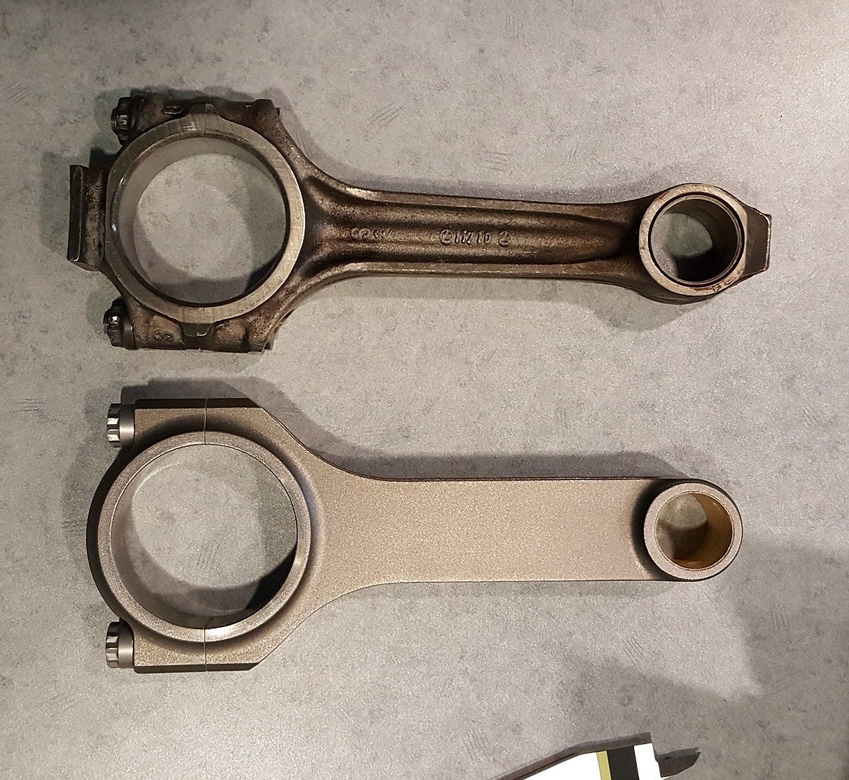 The stock connecting rod is pictured on top, with the new Carrillo rod on the bottom, which is stronger and lighter.