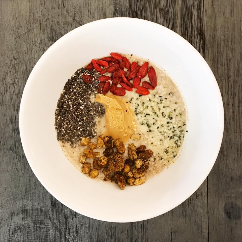 Quinoa Breakfast Porridge: topped with cinnamon, nutmeg, cashew butter, chia seeds, hemp seeds, dried goji berries, dried mulberries, & maple syrup.