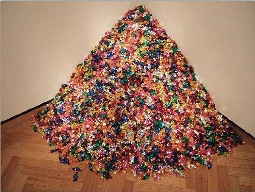 Felix Gonzales-Torres,  Untitled (Portrait of Ross in L.A.)  (1991), multicolored candies, individually wrapped in cellophane, ideal weight 175 lb.; installed dimensions variable, approximately 92 x 92 x 92 cm (36 x 36 x 36 in.)  © The Felix Gonzalez-Torres Foundation.