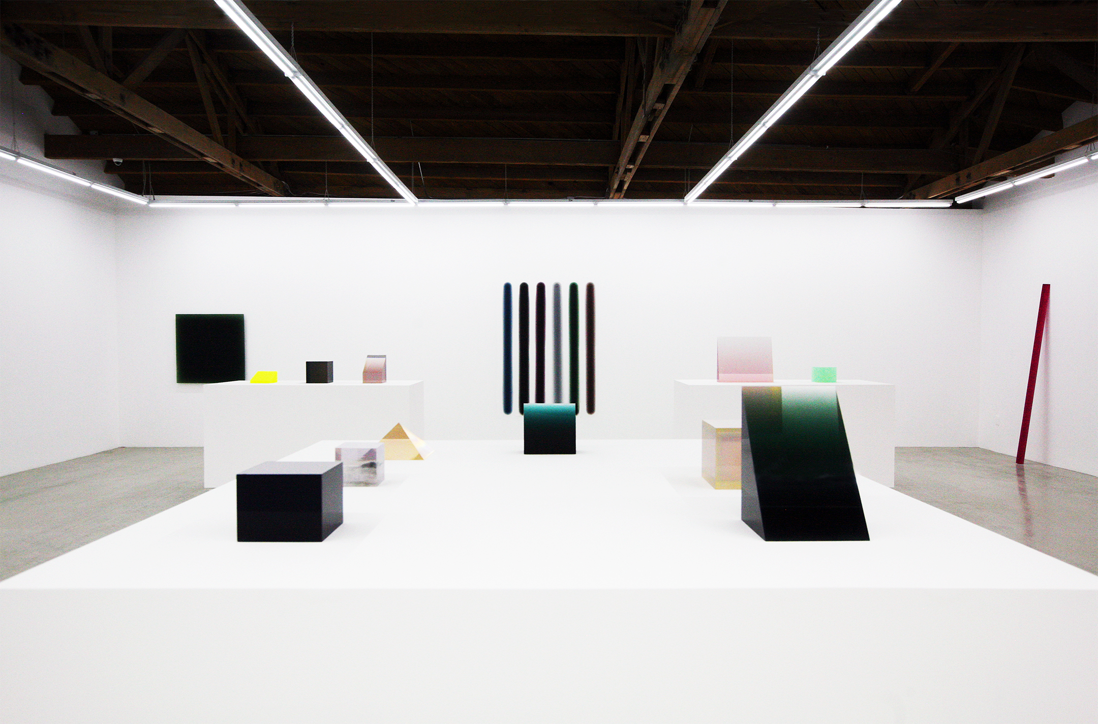 Installation view of Peter Alexander's geometric resin sculptures in various translucent colors