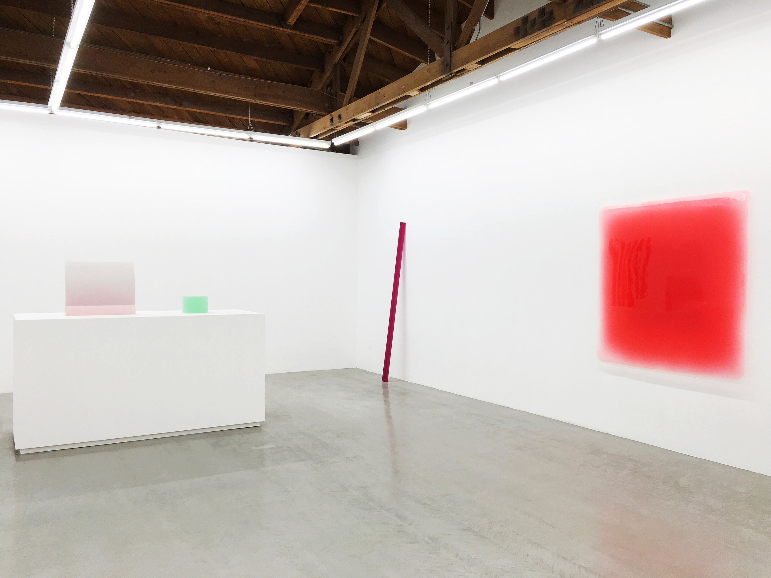 Selection of Peter Alexander's resin sculptures. Large pink translucent block, small translucent turquoise block. Tall thin red block leaning against wall. Wall mounted red resin square