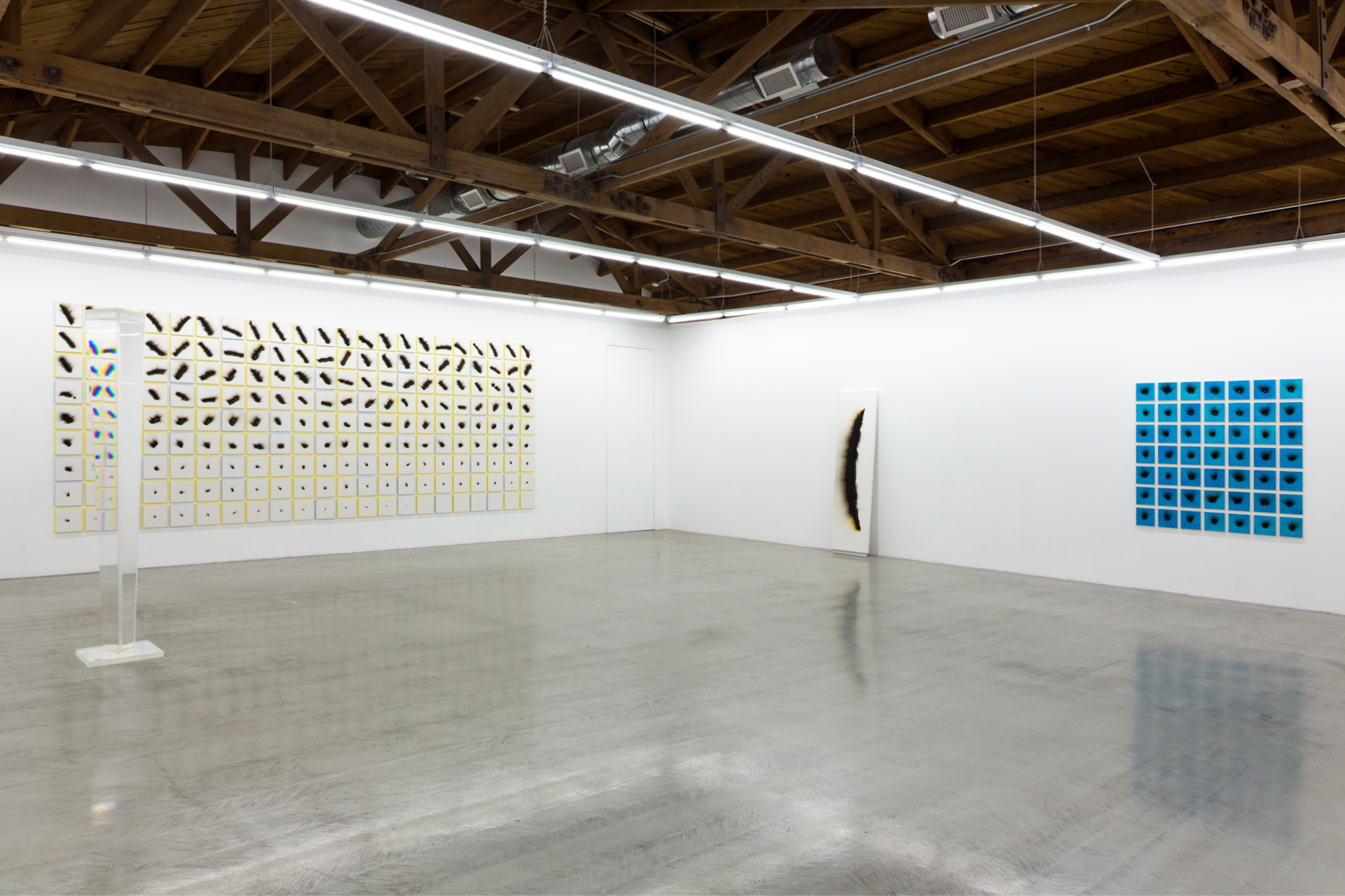 Installation view of Charles Ross' yellow Solar Burns, a large singular Solar Burn, blue Solar Burns and a Prism