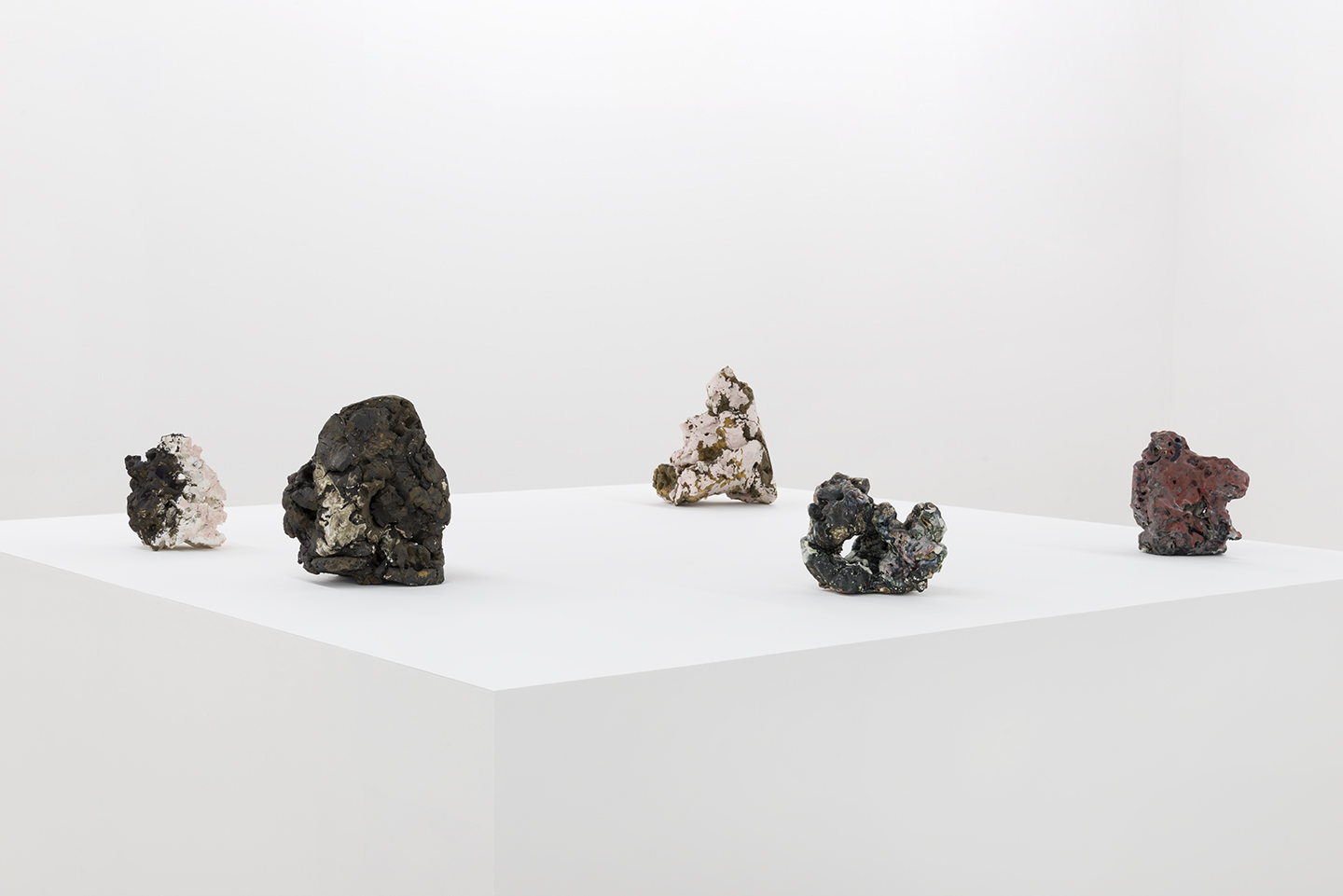 Installation view of Julia Haft-Candell's five abstract ceramic weights on a pedestal