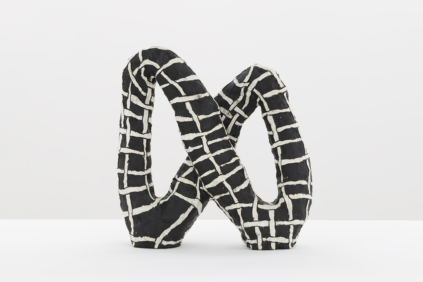 Julia Haft-Candell's Infinity: Weave, a ceramic sculpture of an black infinity with interwoven white stripes