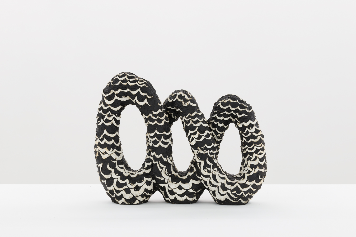 Julia Haft-Candell's Infinity: Water, a black ceramic infinity with three looks and raised white waves