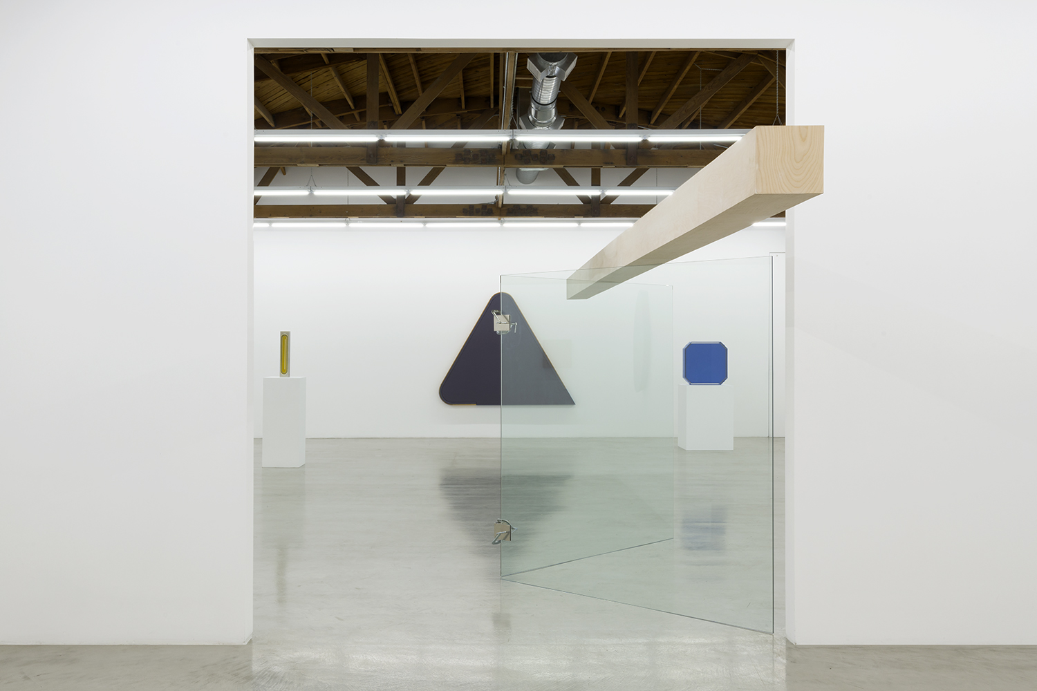 Installation view of Tony Delap: A Career Survey, with Floating Lady II two glass panels connected by metal bits with a large wooden beam set on top at the center of the image