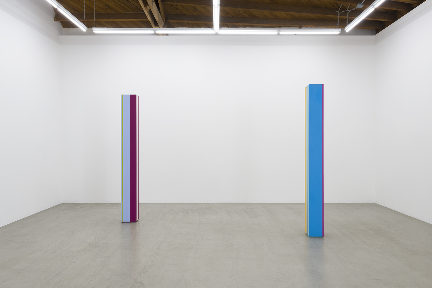 A front installation view of the two Anne Truitt sculptures in the show, showing vertical stripes of magenta, teal, blue, yellow and pink