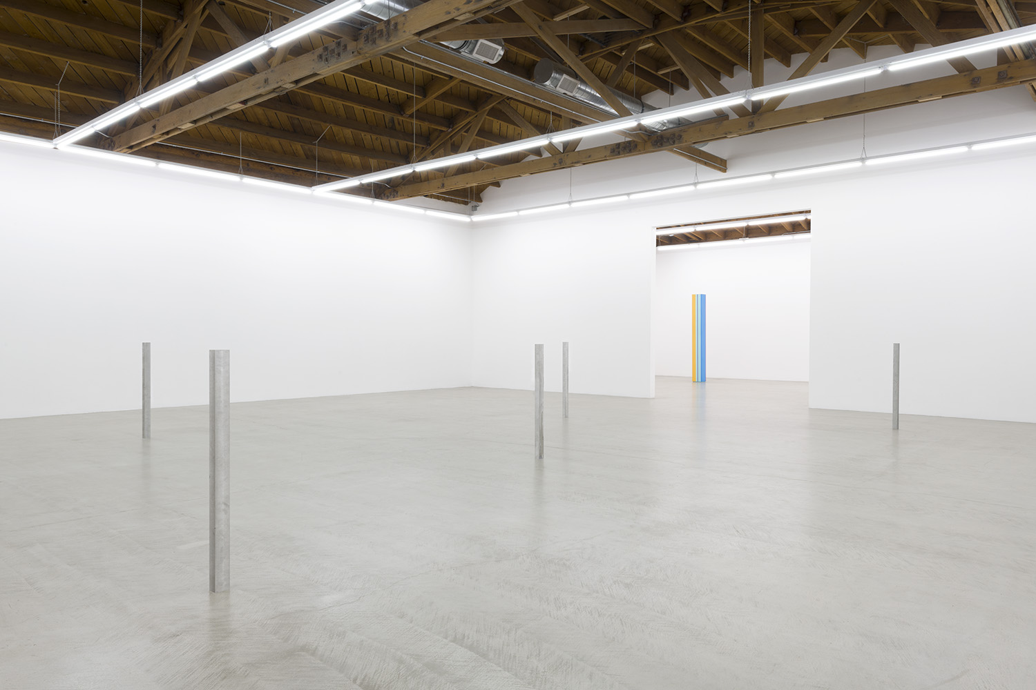 Installation image of all five aluminum and steel cast sculptures standing erect methodically placed within the gallery, an Anne Truitt is also visible in the back