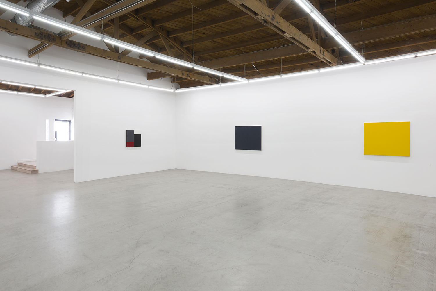 Installation of three of Edith Baumann's paintings, the early grid piece, and the grey and yellow monochrome paintings