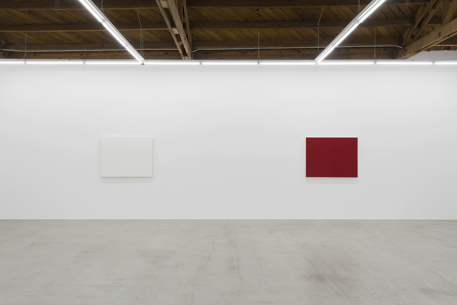 Installation view of two of Edith Baumann's monochrome paintings, white and red