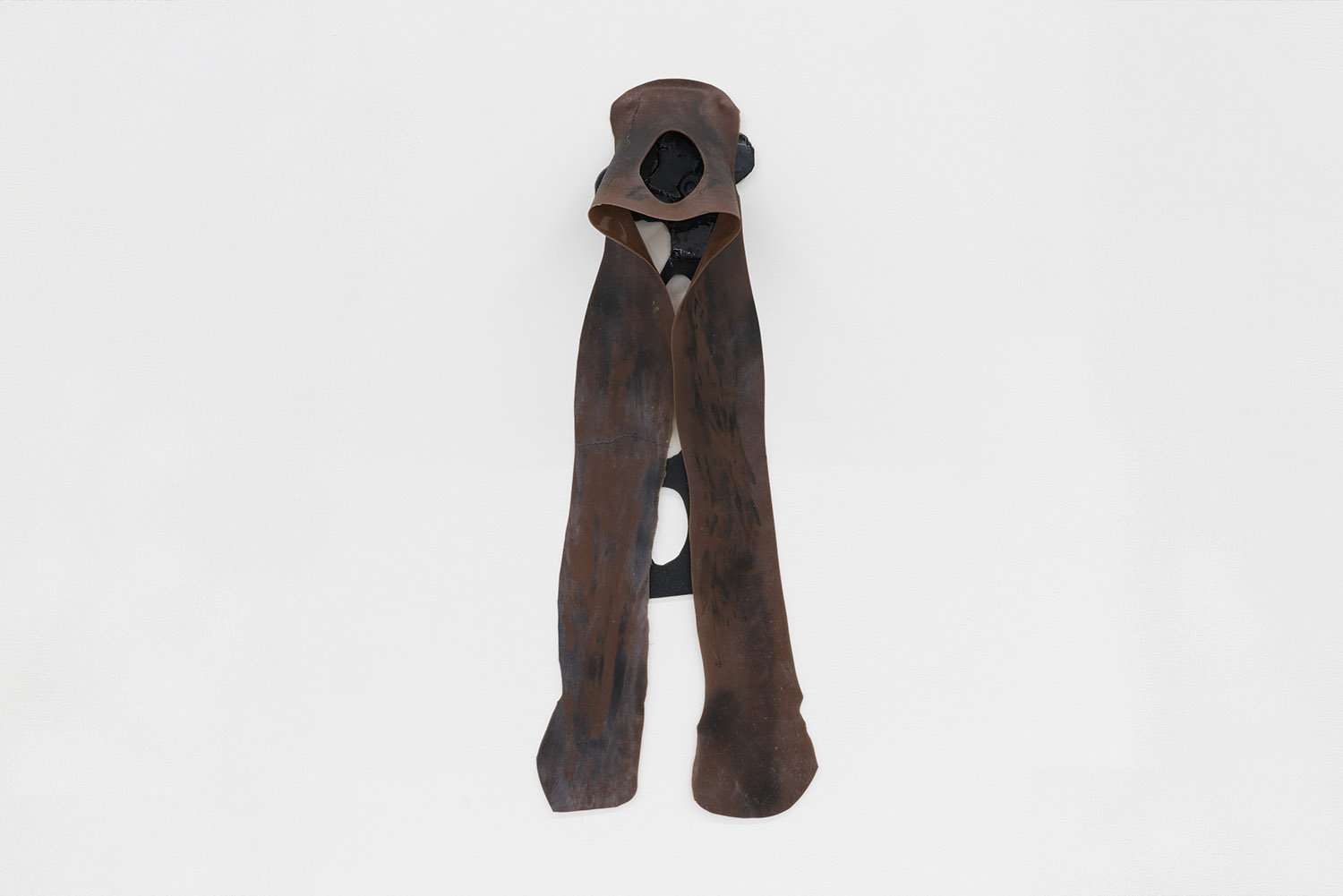 Copy of Sara Gernsbacher's abstract sculpture made of silicone and acrylic paint resembling a brown hood with legs over a black flower with a black stem hanging against a white wall