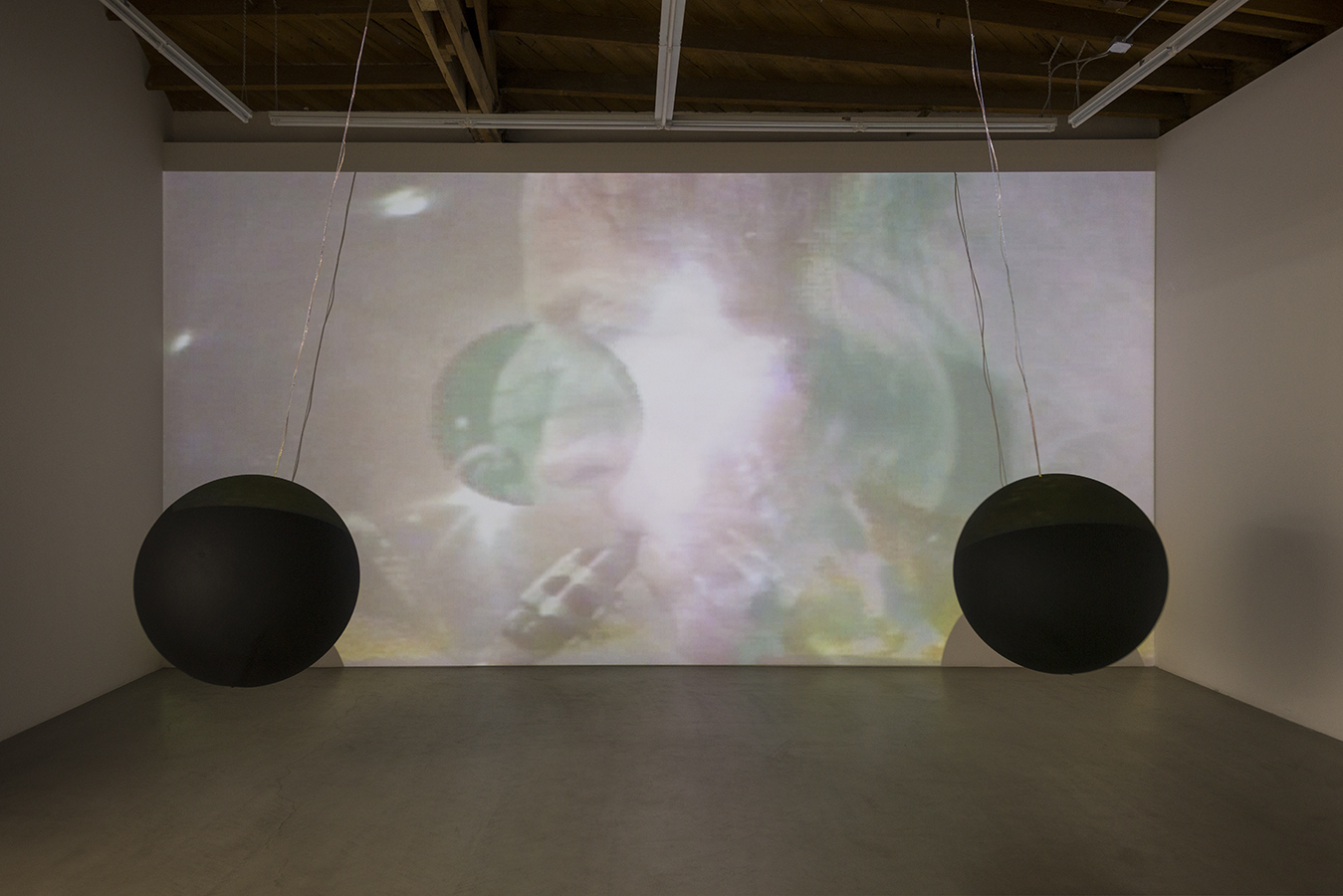 Installation View of Arlo Acton and Terry Riley's Music with Balls Video with the original Acton speaker spheres in front