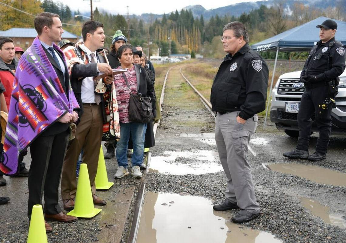 Ryan Dreveskracht and Gabe Galanda, at left, at Nooksack, facing off with the Tribal Police Chief