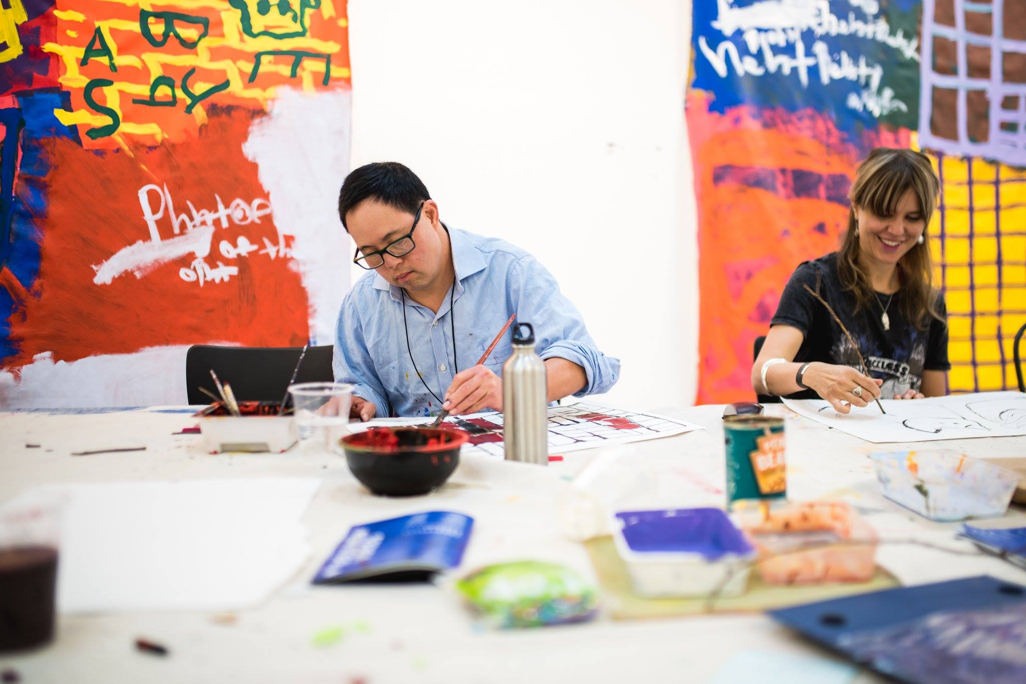 Image: Studio A supported artist, Damien Showyin, leading a painting workshop.