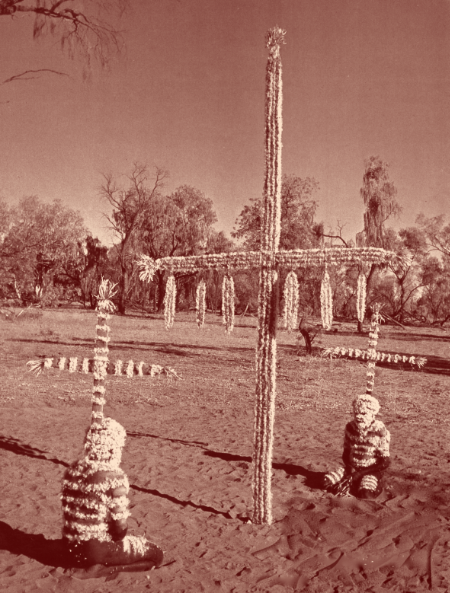 La croix en bois est le symbole de la subincision du pénis imposée à tous les hommes Arranda par la tradition. Le duvet d'aigle est collé sur le corps avec le propre sang des acteurs.