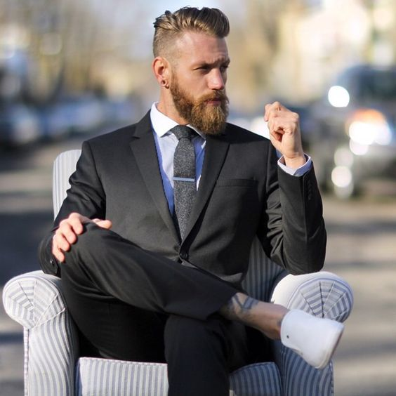 Fashionable man with beard on armchair in street