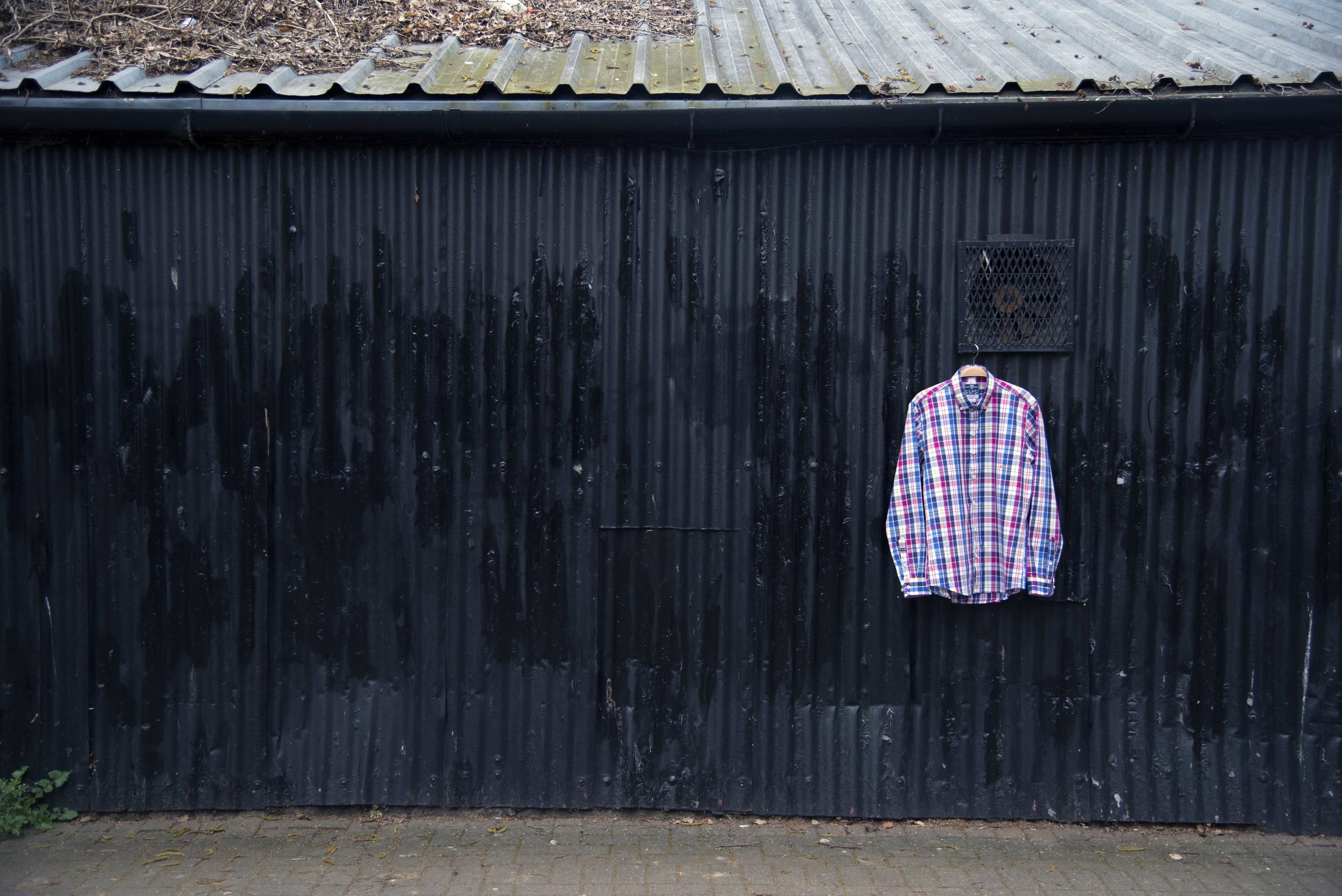 Mans checked shirt hanging off a corrugated door in Hereford