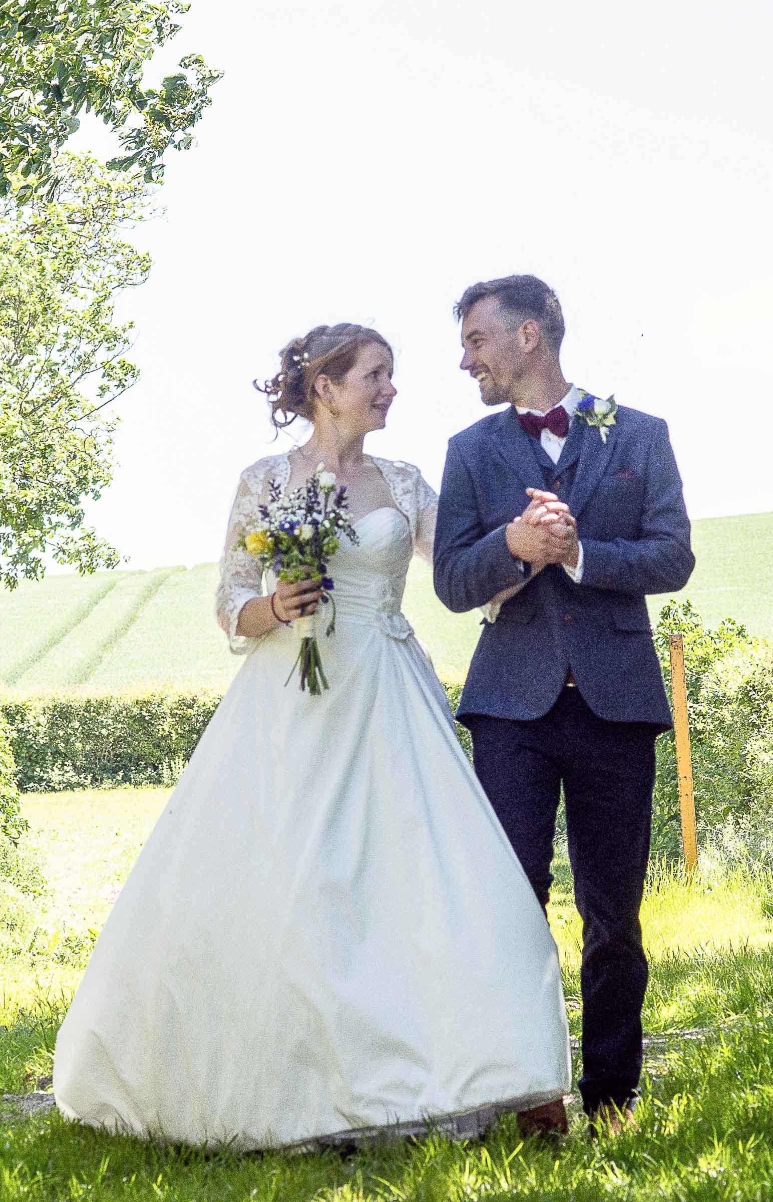 Bride and groom walking through a summer field