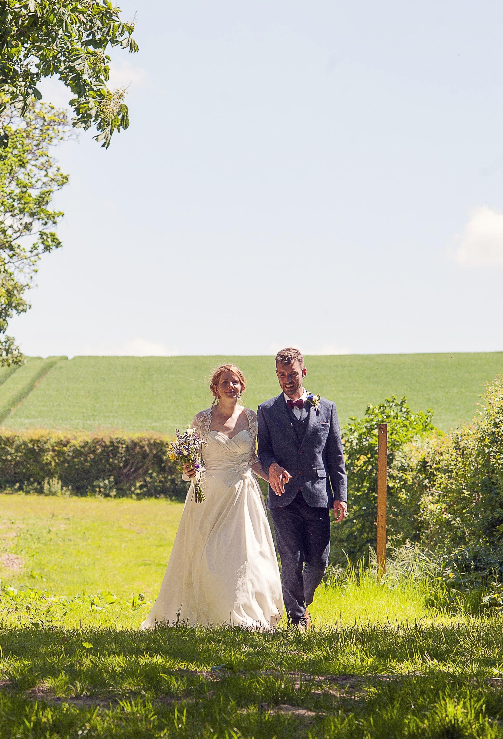 Wedding couple strolling through a summer field