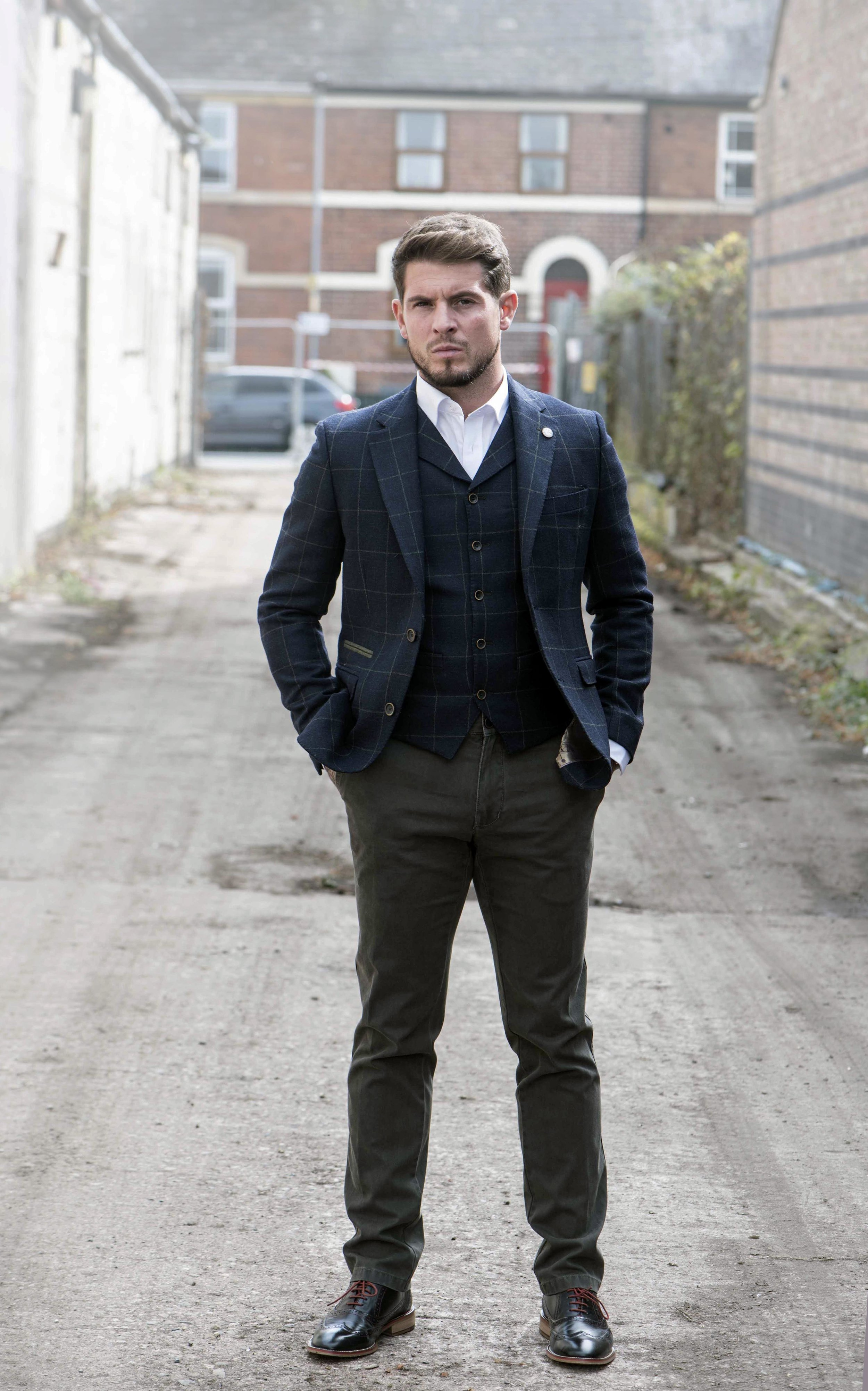 Man in check waiscoat, jacket and blue trousers.jpg