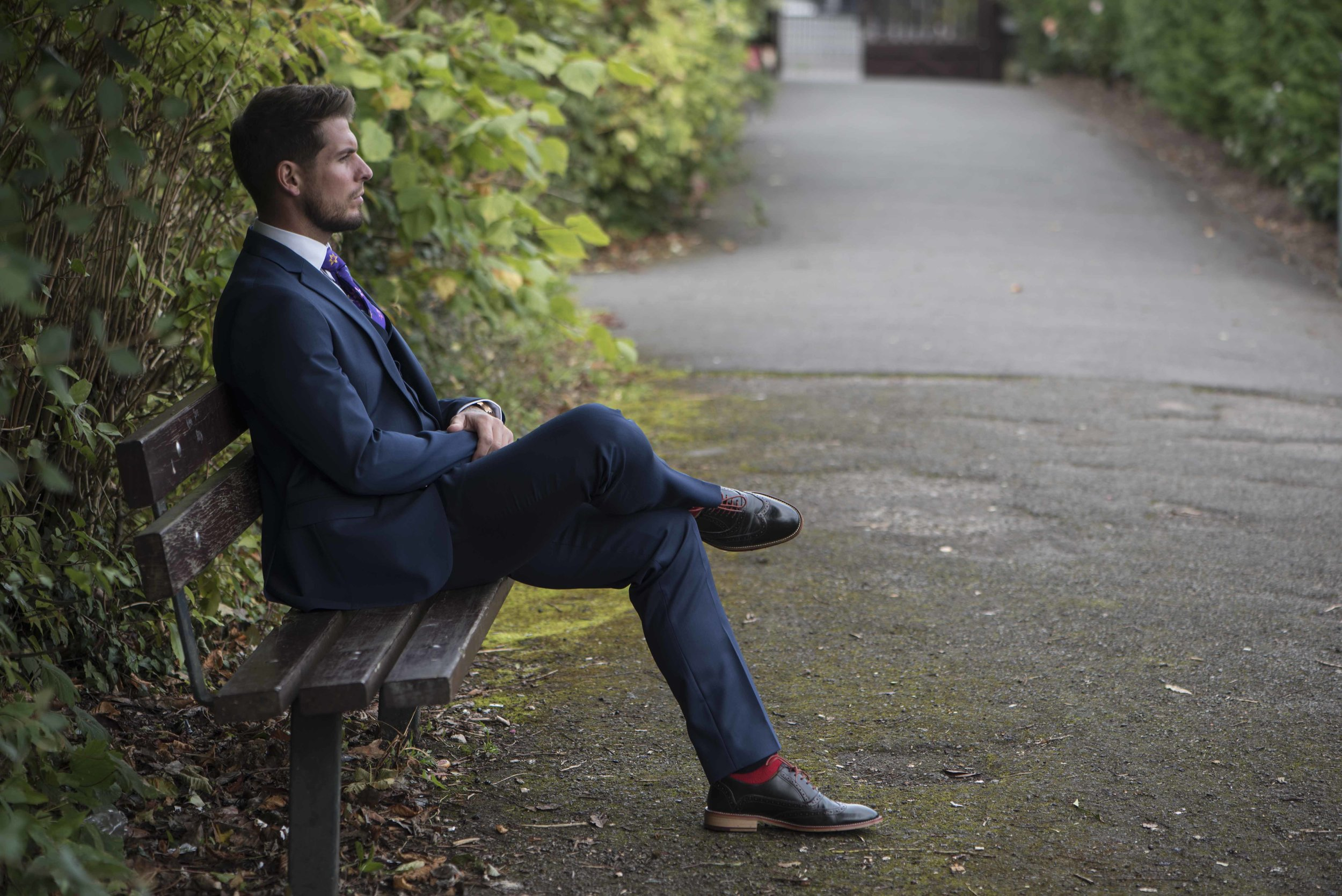 Man in suit sitting on park bench