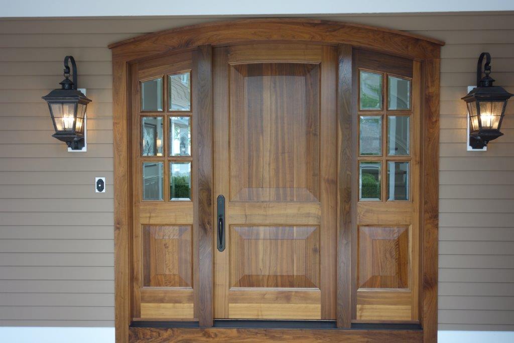 Raised panel black walnut entry door with beveled glass side lites.