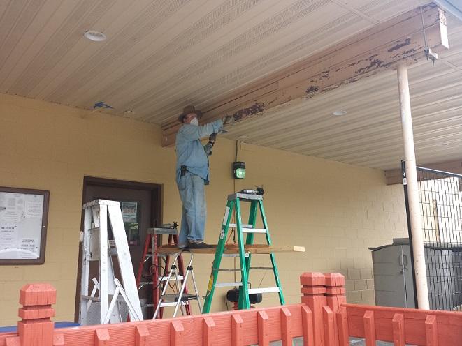 Bill Robbins sanding the support beams on 6-19-2018.jpg