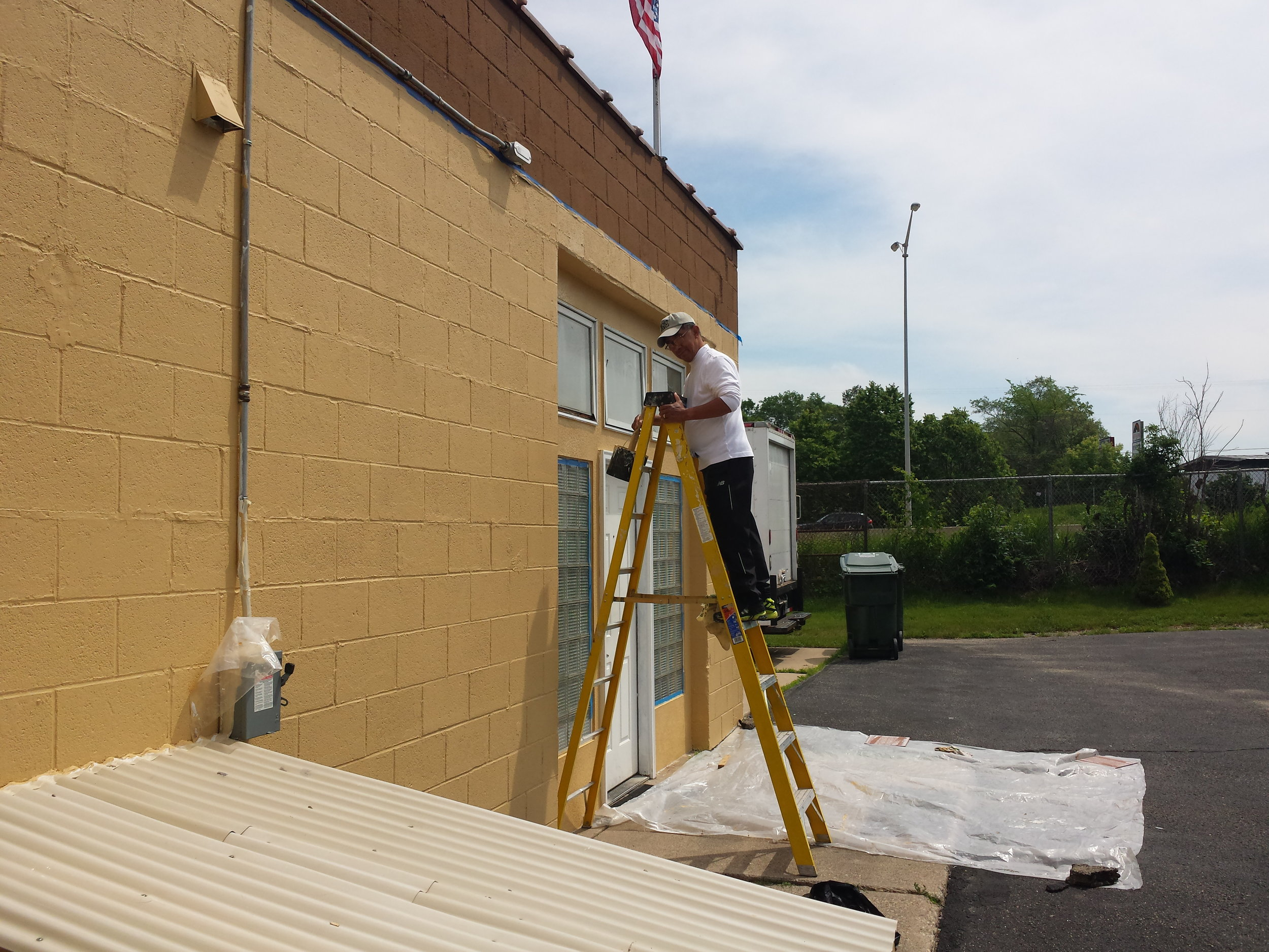Legionnaire Romeo applying finishing touches to the painting of Post 501, July 2018.
