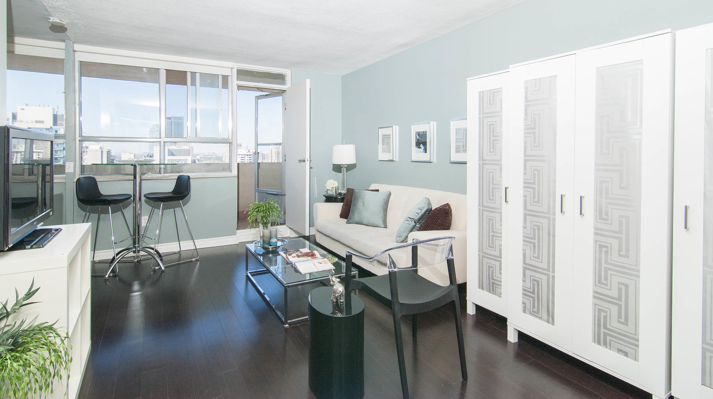 Toronto living room with white couch - IKEA storage -glass coffee table - bamboo flooring.jpeg