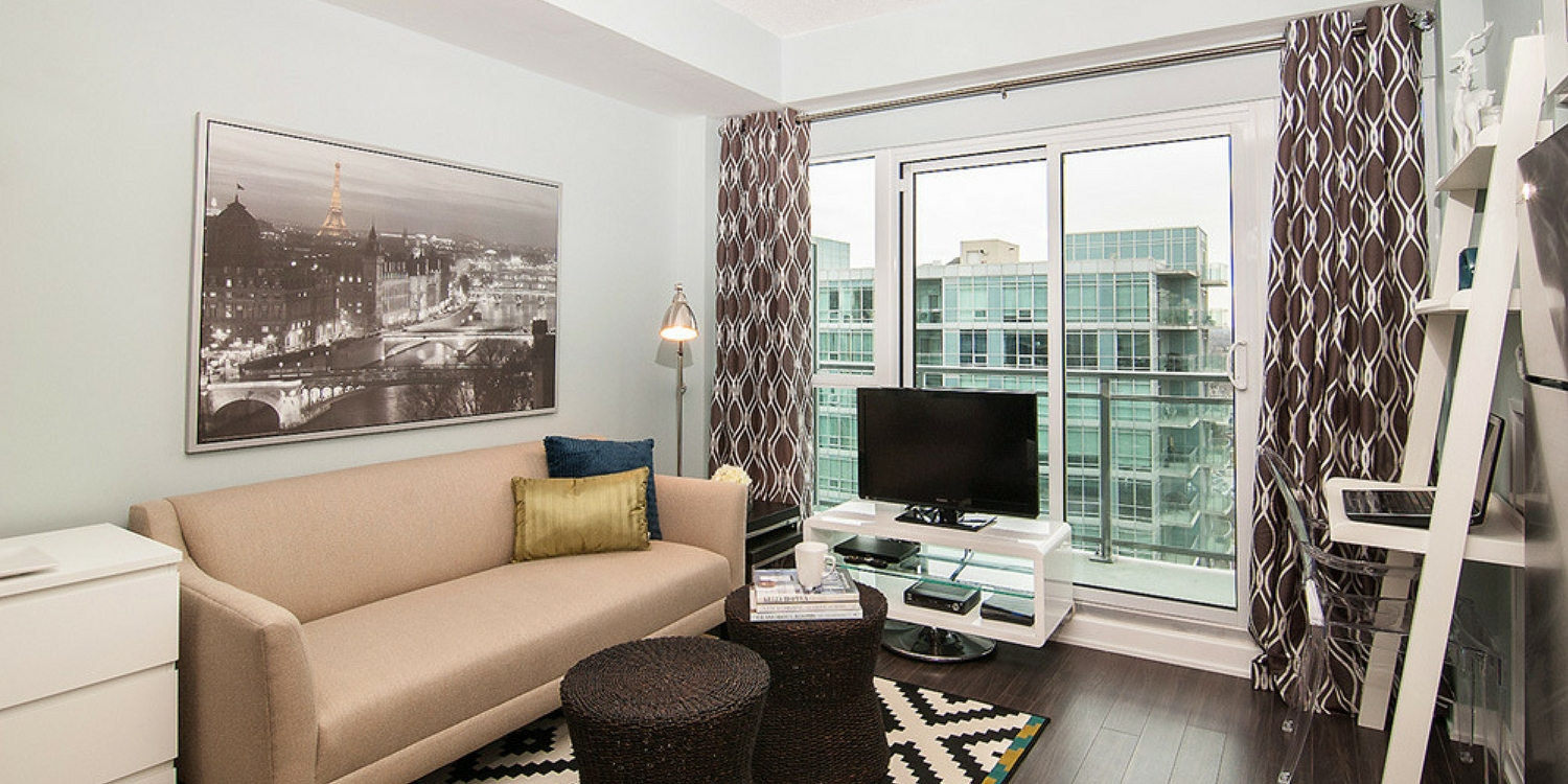 Toronto condo living room with pale brown colours and dark floor - patterned curtains on the patio door - seagrass stools as coffee table.jpeg