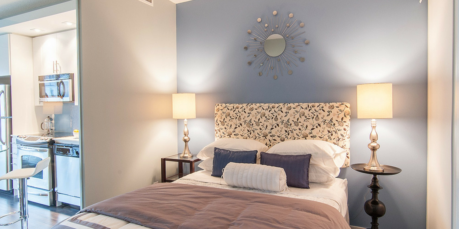 Small Toronto condo bedroom with black and yellow headboard-blue accent pillows-blue accent wall-fun mirror as wall art.jpeg