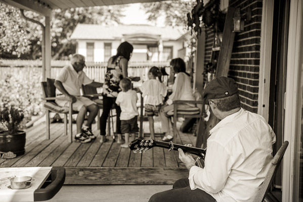 Man plays guitar while family sits at picnic table in background