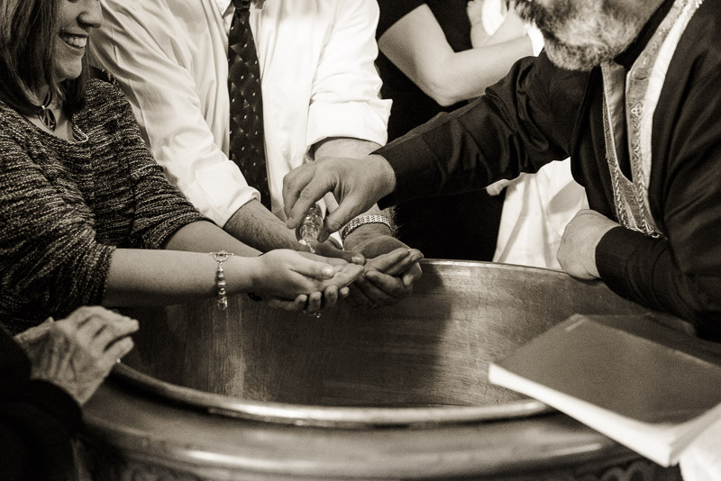 Annointing the hands of the godparents during the baptism.