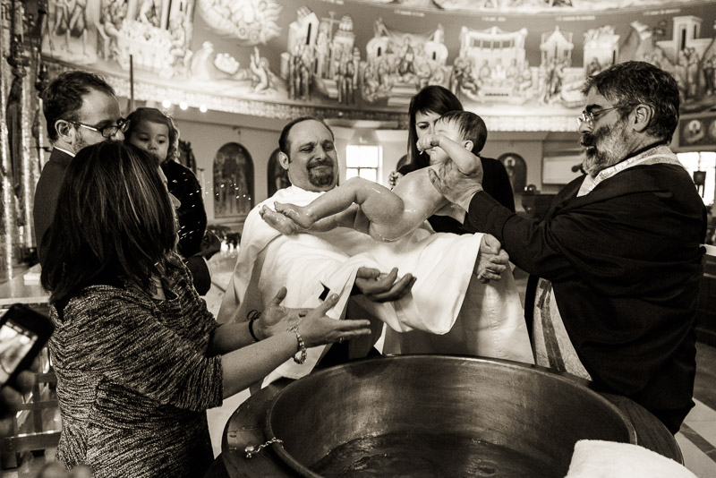 Water flies and laughter ensures as the baby is brought out of the baptismal font.