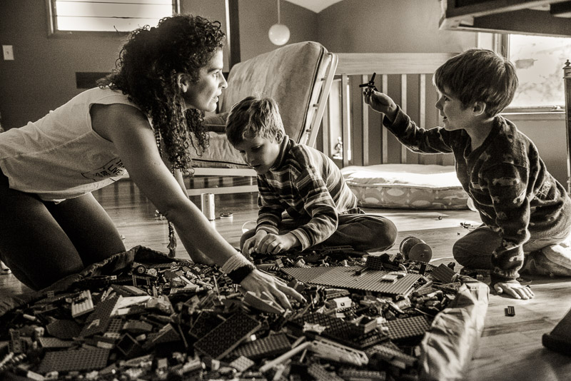 photo of woman and two boys playing with Legos