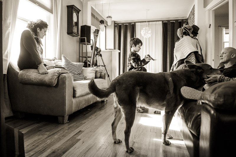 Group documentary photo of family in living room with their dog.