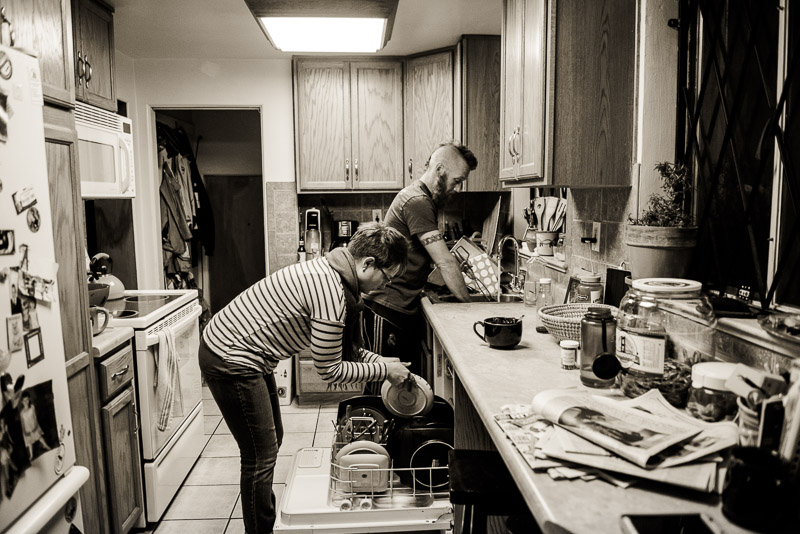 Mom and dad clean up the kitchen.