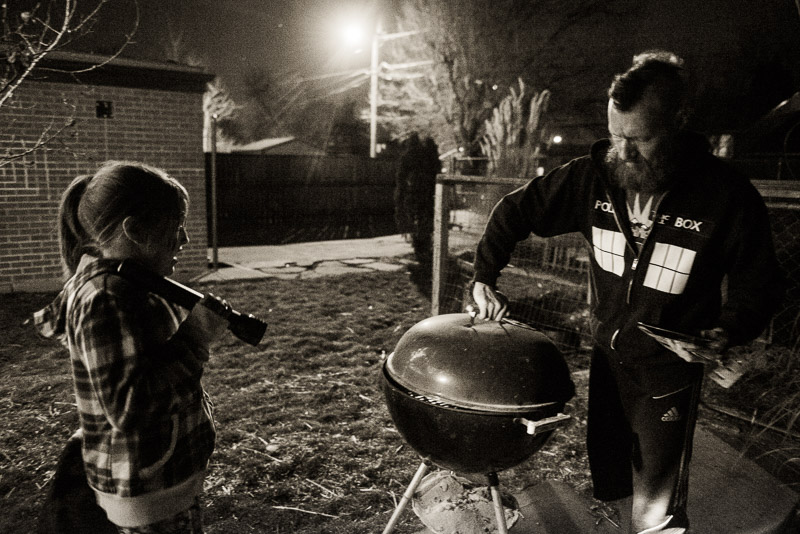 Man and girl grilling and holding a flashlight.