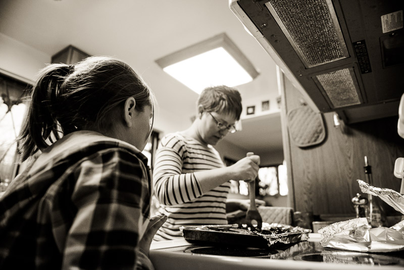 Girl looks on as mom cooks dinner.