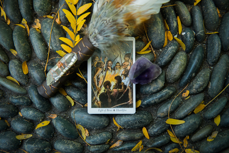 The Hearthfire tarot card, a feather, and a piece of crystal