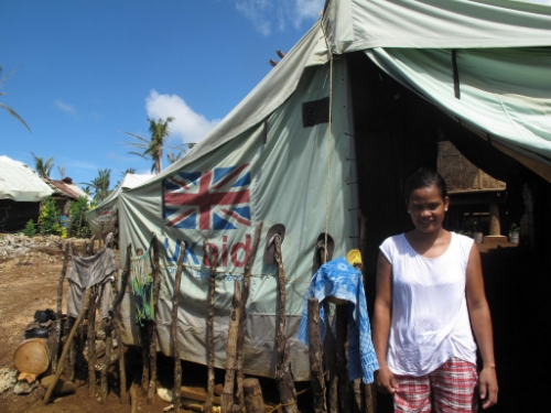 A young woman standing outside a UK Aid tent in the Philippines following a Typhoon. Image Credit:  DFID  via  Flickr   cc