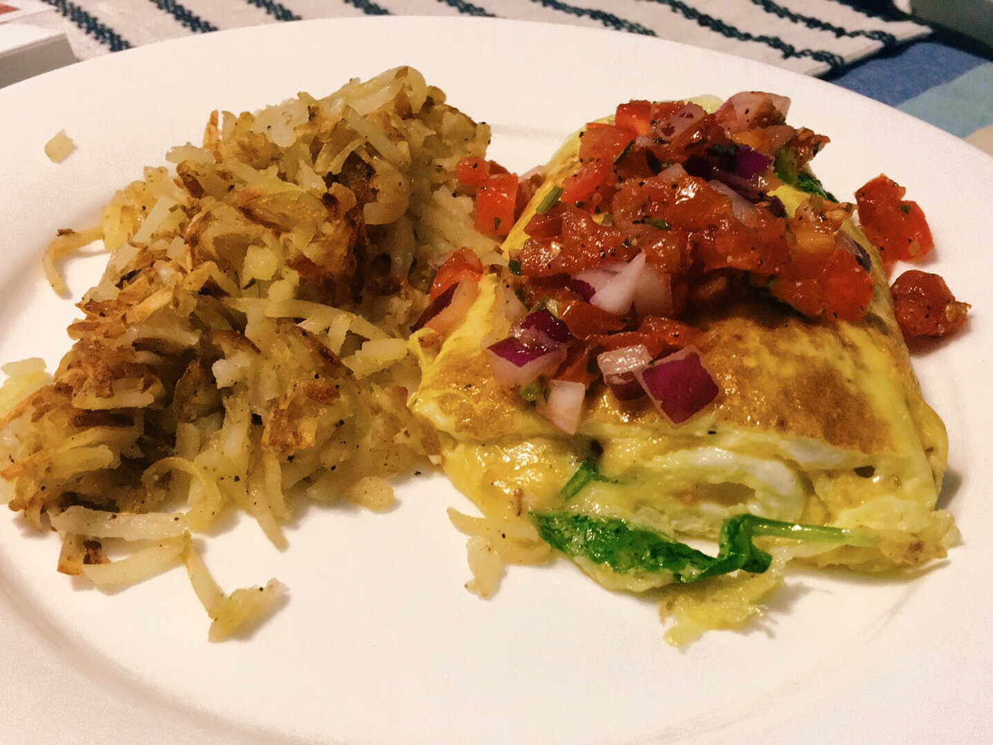 Hash browns and an arugula omelette topped with pico de gallo.