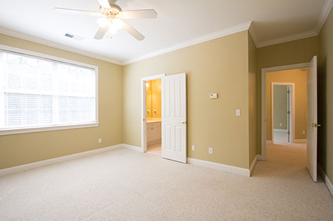 Wow, look at the those windows! It's like a nuclear bomb is going off outside. Can you tell there are blinds? Also, the lights on the ceiling fan are glowing and blown out. There is light in the bathroom and hallway, but they both look like the paint is orange instead of the same color as the bedroom.