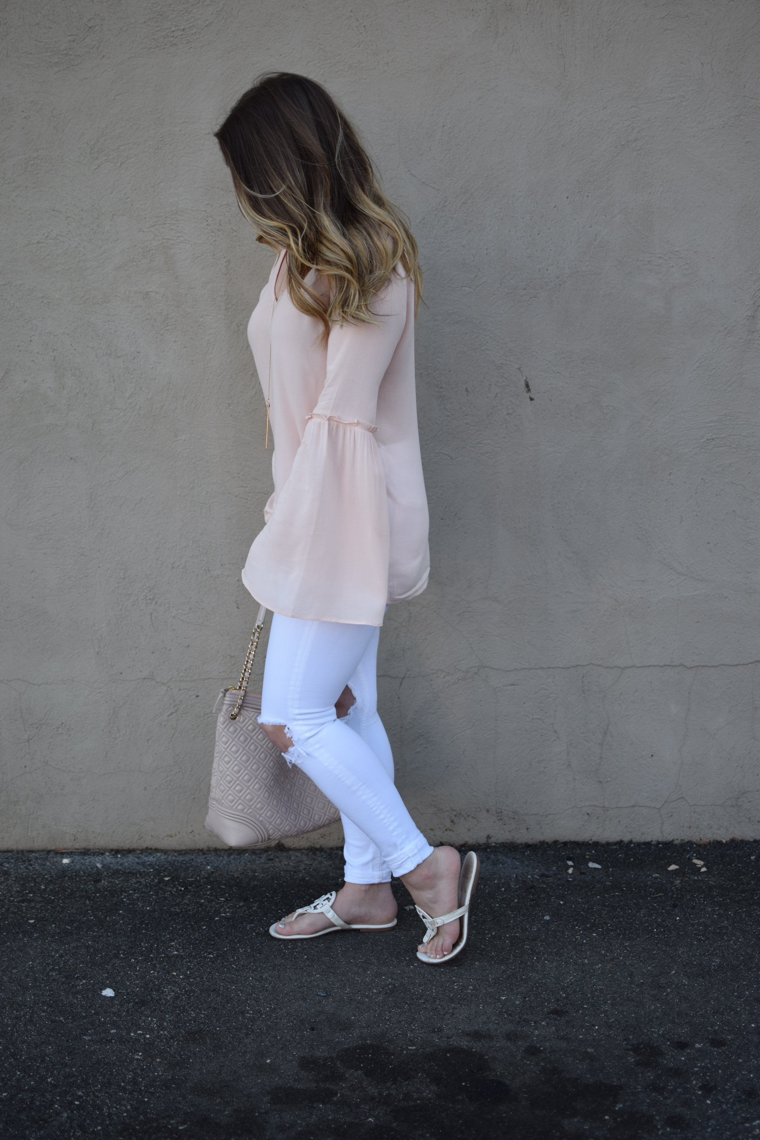 blush bell sleeve top / white distressed denim / tory burch miller sandal / spring outfit idea / balayage hair
