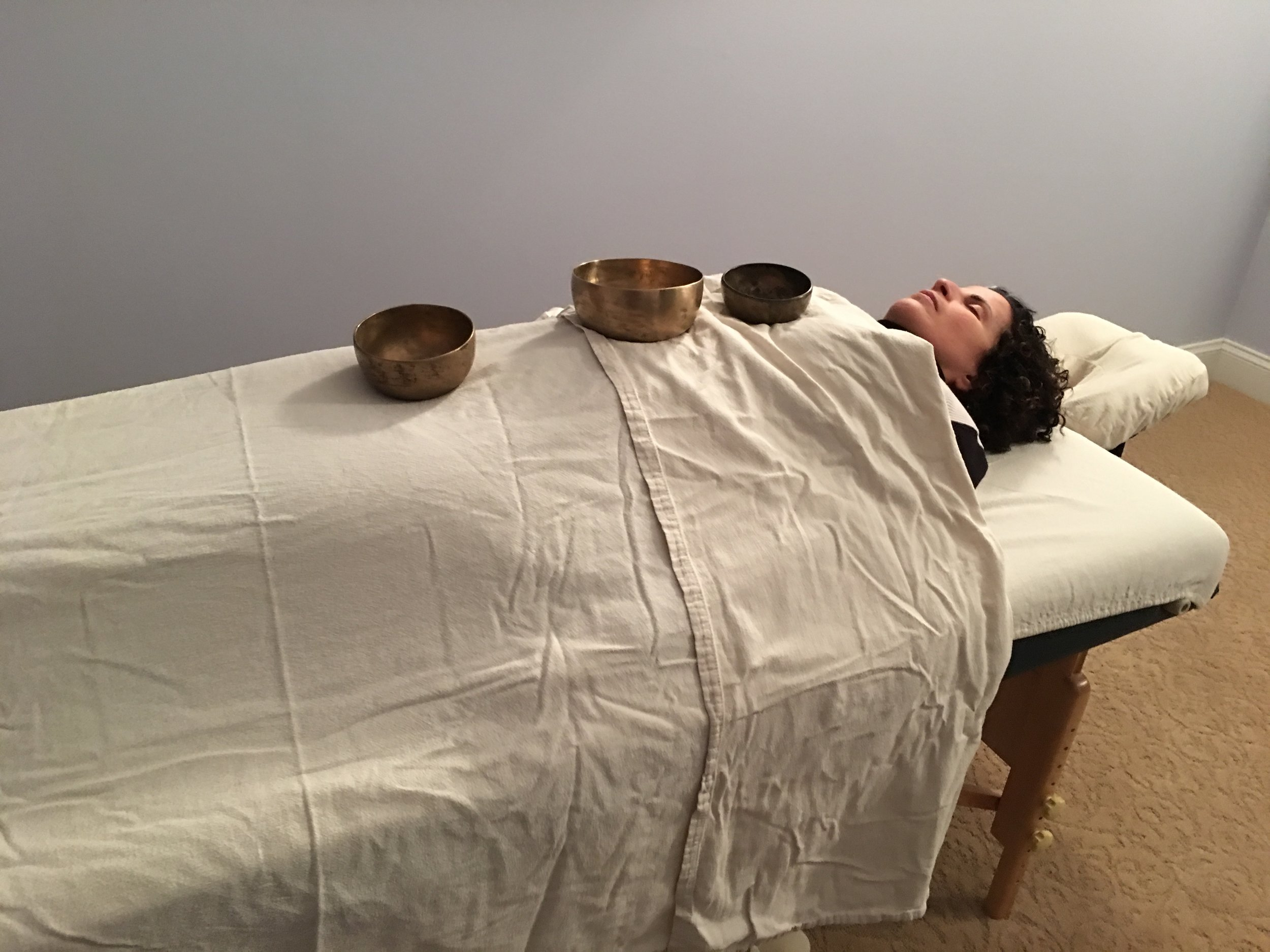 Antique sound bowls are placed on or around the body to clear old energies and open healing pathways.