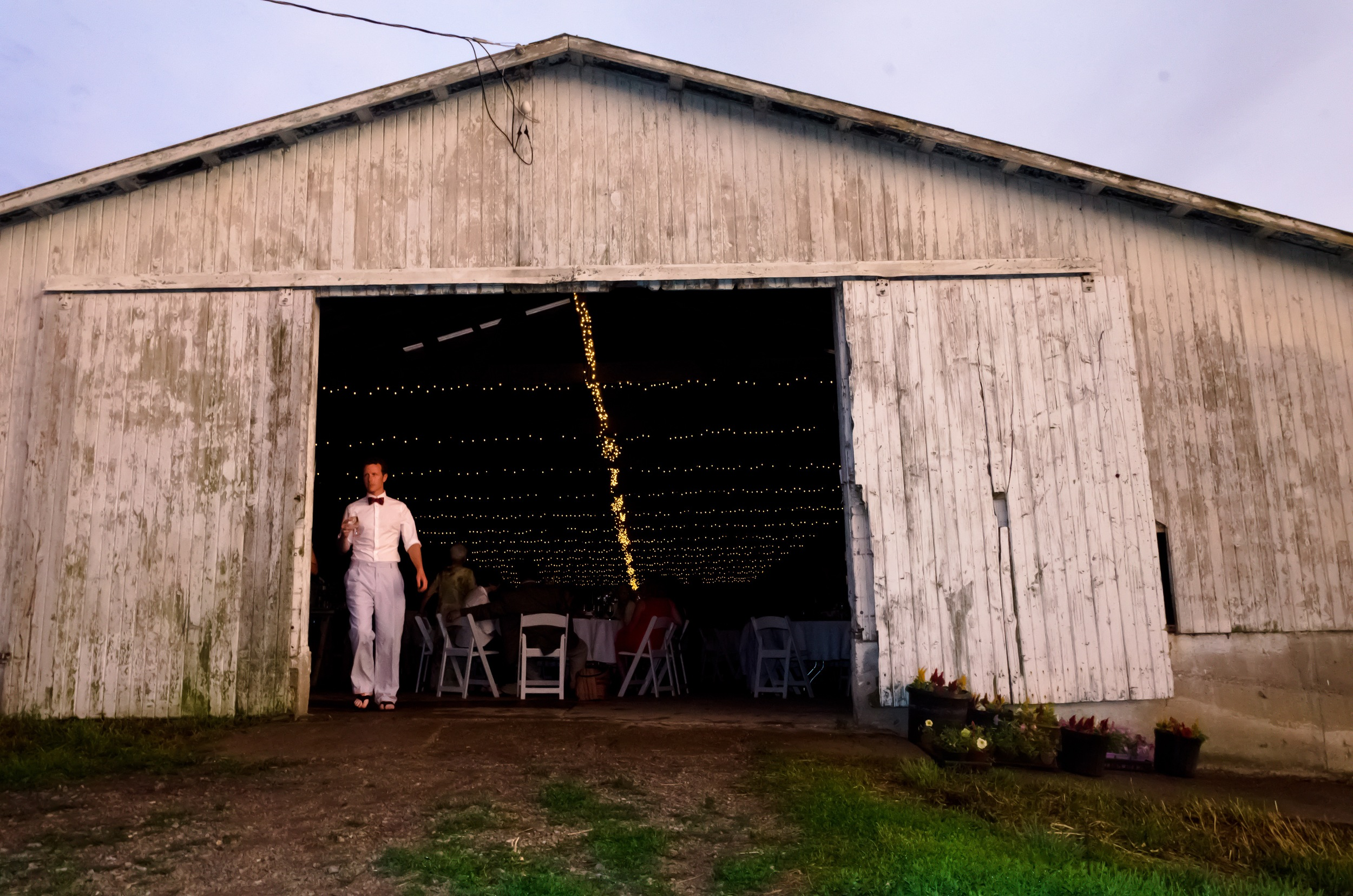 My wedding, years later, with the tractor hole remaining on right hand door of the barn. Photo by Patricia Black McCauley