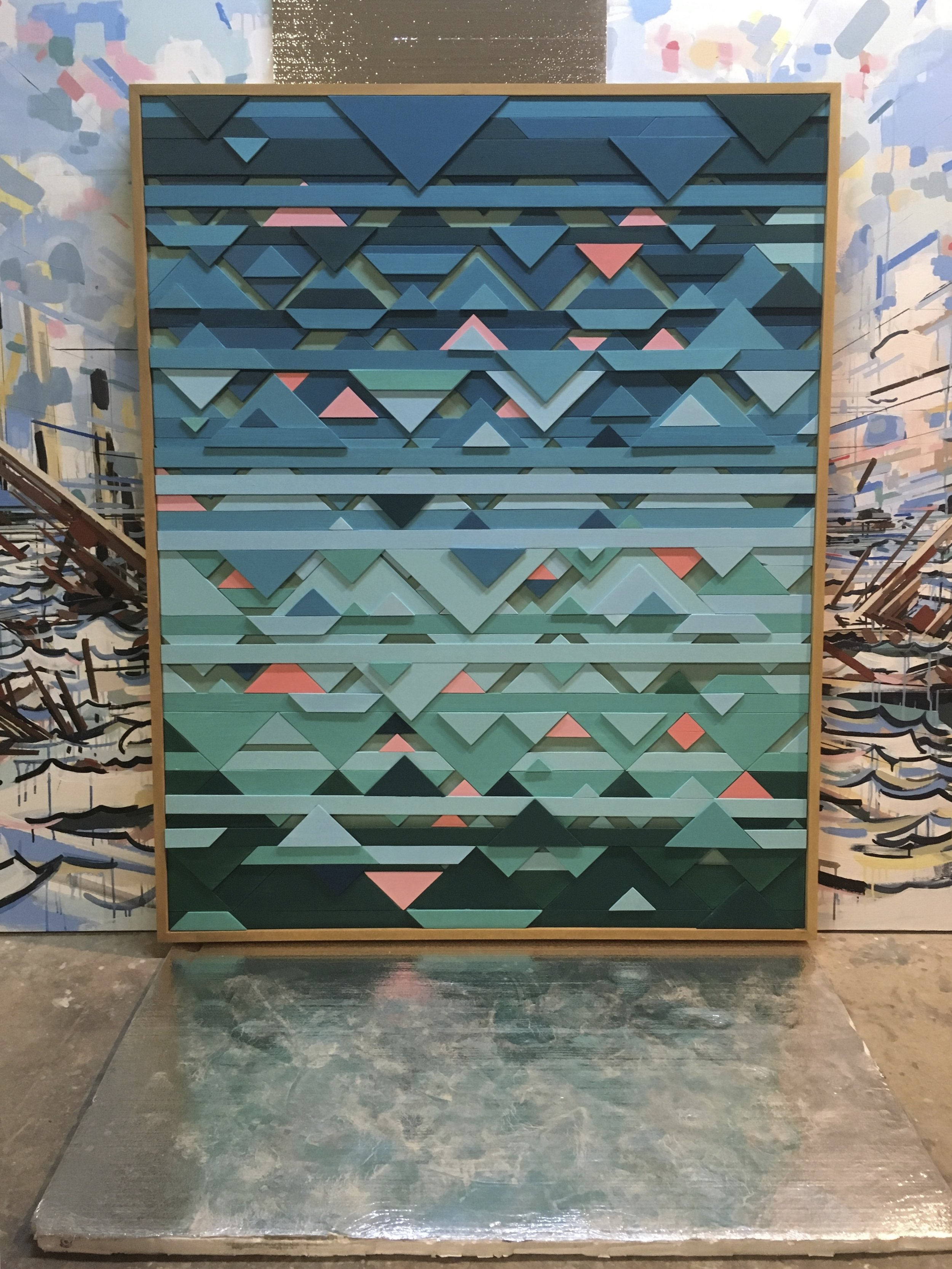 """Triangulated Horizons. 48x60x3"""". Wood, paint. Private Collection Austin, TX. Background: 8x24' painting in progress."""