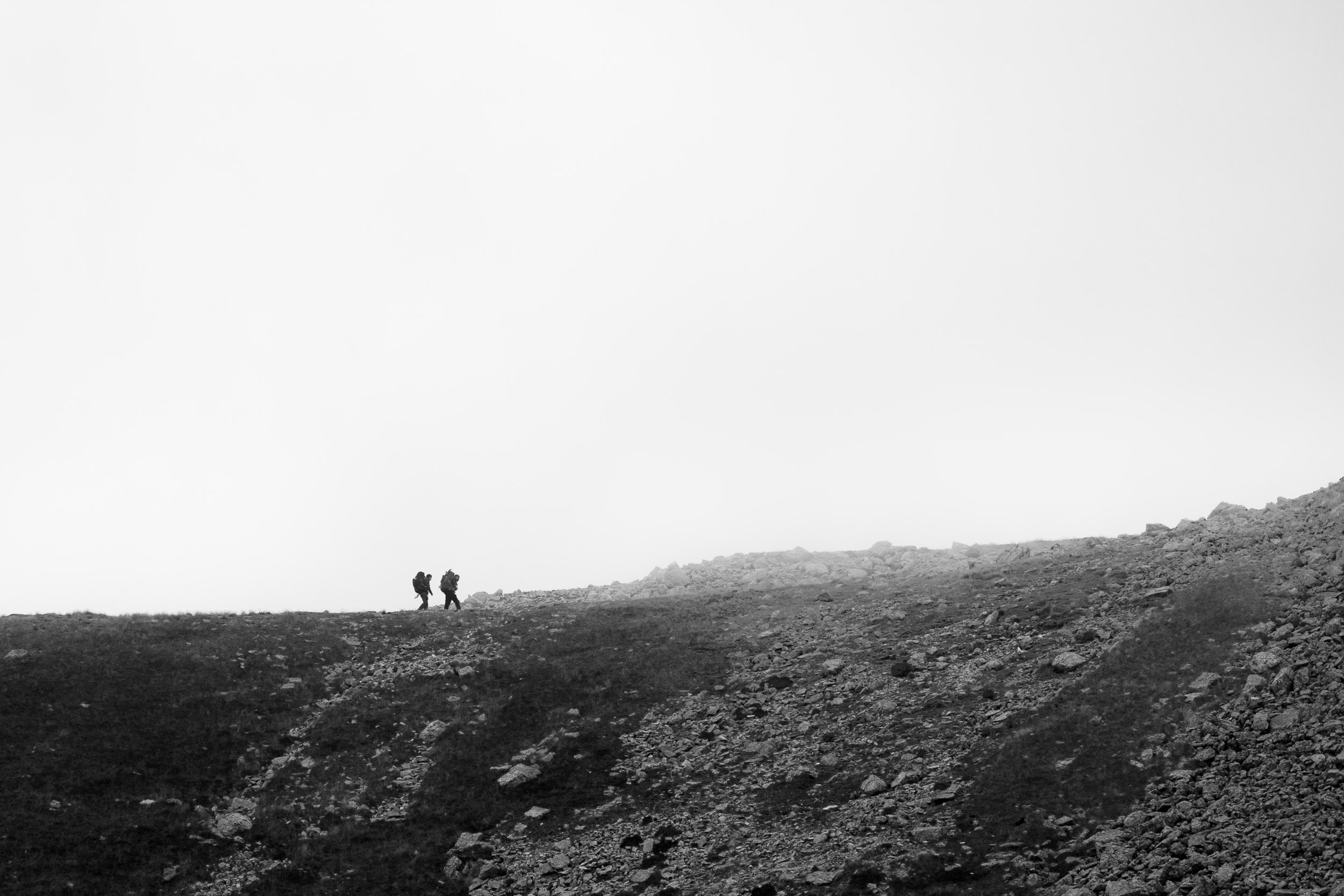 hikers ascending great end lake district national park england uk.jpg